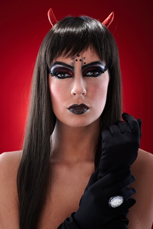 Portrait of devil like woman with professional black makeup and horns. photo