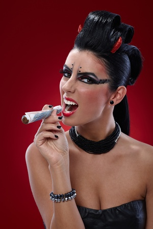 wicked woman: Provocative wicked woman looking like devil smoking banknotes. Stock Photo