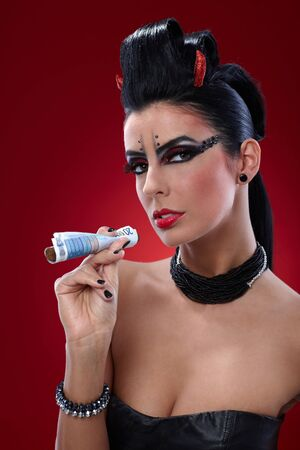 Provocative devil like woman smoking banknotes. photo