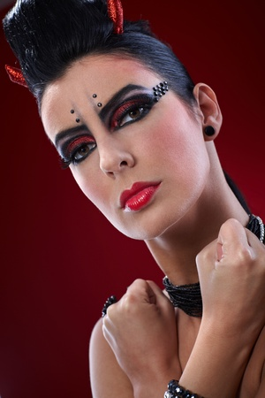 Closeup portrait of devil woman with clenched fists and professional makeup. photo