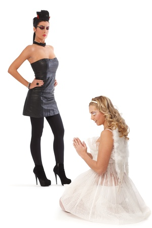 angry angel: Devil and angel, good and bad. Angel praying, devil looking angry. Stock Photo