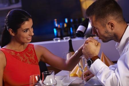 be kissed: Loving couple having dinner in restaurant, man kissing womans hand, smiling. Stock Photo