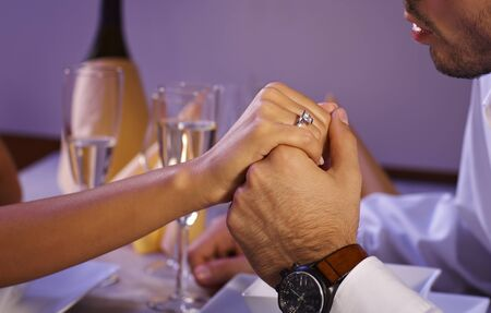 be kissed: Man and woman holding hands at dinner table. Woman in engagement ring.