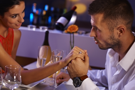 be kissed: Attractive loving couple holding hands at dinner table, looking affectionate.