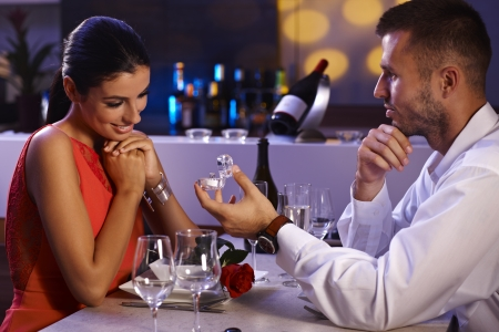 Jonge man stelt voor om mooie vrouw, die verlovingsring, wachtend op antwoord.