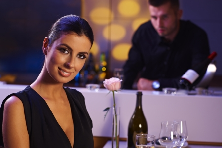 Elegant young woman sitting in restaurant, smiling happy. Bartender watching from background. Stock Photo - 16859294