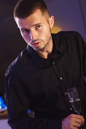 night club: Giovane uomo in camicia nera che tiene flute di champagne.