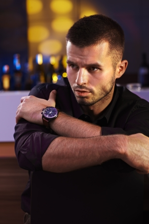 Evening portrait of young man in black shirt, looking away. Stock Photo - 16859319