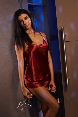 sexy woman standing: Sexy mujer de pie junto a la pared con un pijama de seda roja con champ�n para dos. Foto de archivo