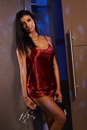 nightdress: Sexy woman standing by wall in red silk pyjamas with champagne for two. Stock Photo