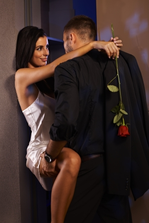 nighty: Romantic couple embracing at home, woman in silk nighty holding rose.