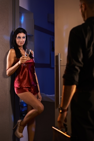 invitando: Sexy mujer de pie en la puerta del dormitorio en piyama de seda roja, el hombre saludo llegar del trabajo. Foto de archivo