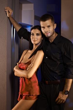 nighty: Happy couple standing at door, woman in sexy pyjamas, both smiling.