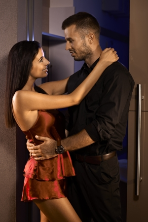 be kissed: Young man and sexy woman in silk pyjamas embracing in bedroom door. Stock Photo