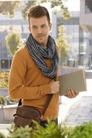 sueter: Retrato del estudiante masculino que sostiene al aire libre libros.