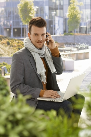 citypark: Young businessman sitting in citypark, talking on mobilephone, using laptop computer.