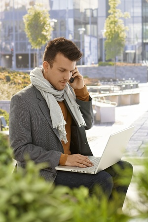 citypark: Young man sitting in citypark, using laptop computer, talking on mobilephone. Stock Photo