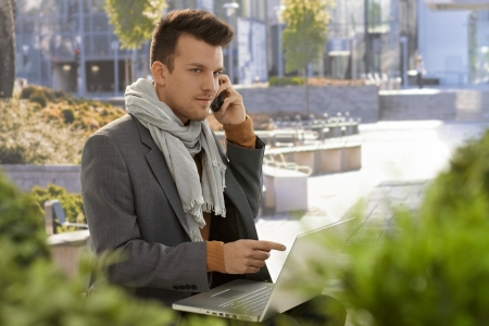 Young businessman sitting in citypark using mobilephone and laptop. photo