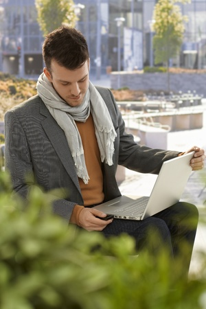 citypark: Young man sitting in citypark, using laptop computer, inserting USB flash drive.