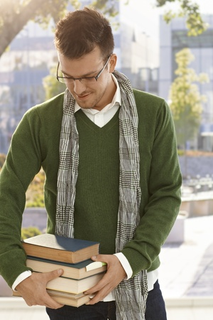 Male student holding pack of books outdoors. photo