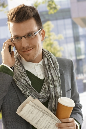 calling on phone: Happy young businessman talking on mobile, holding newspaper and coffee outdoors. Stock Photo