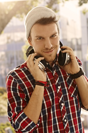 Modern young man standing outdoors, using headphones, smiling. photo