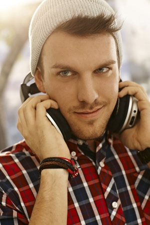 20s  closeup: Closeup portrait of trendy young man listening to music through headphones outdoors. Stock Photo
