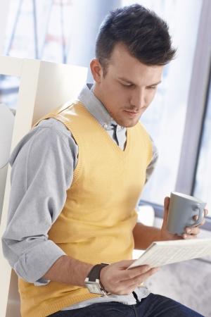 hombre sentado: Hombre joven que lee las noticias, tomando un café-break.