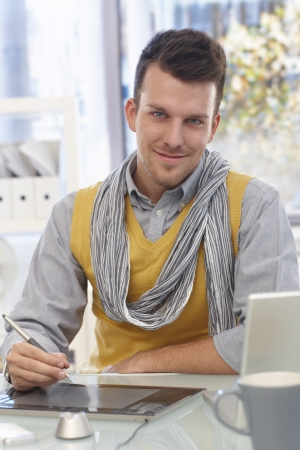 Handsome young man sitting at desk, using drawing pad, smiling, looking at camera. photo