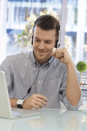 Happy young man working at callcenter, using headset, smiling. Stock Photo