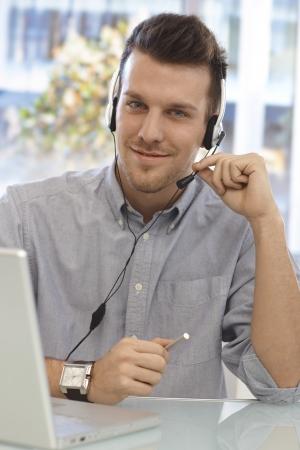 dispatcher: Portrait of happy male dispatcher sitting at desk, using headset. Stock Photo