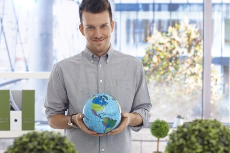 Portrait of young man holding globe, smiling, looking at camera. photo