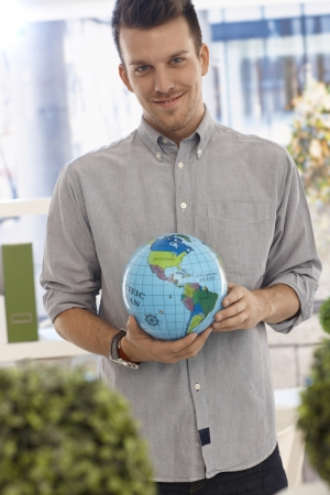 Happy young man holding globe in hand, smiling. photo