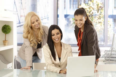 Happy businesswomen working together on laptop computer at office, smiling. Stock Photo - 16890541