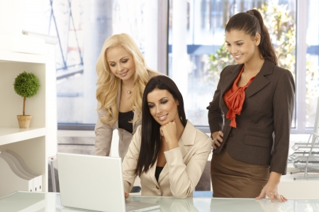 Happy businesswomen working together on computer at desk, smiling. Stock Photo - 16890540