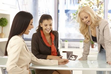 Happy young woman showing baby scan to colleagues at office. Stock Photo - 16859371