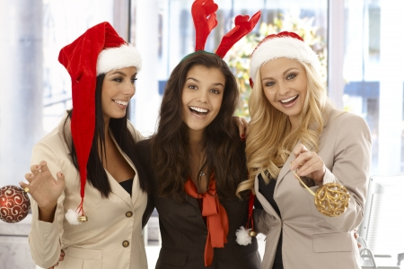 Young businesswomen celebrating Christmas at office wearing santa claus hat. Stock Photo - 16859538