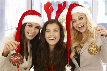 Young businesswomen celebrating Christmas at office wearing santa claus hat. Stock Photo - 16764853