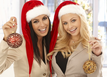 Young businesswomen celebrating Christmas at office wearing santa claus hat. Stock Photo - 16859399