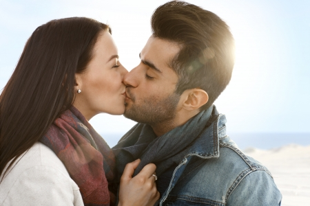 be kissed: Romantic young couple kissing on the beach at autumn. Stock Photo