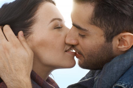 hugs and kisses: Closeup photo of young loving couple kissing.