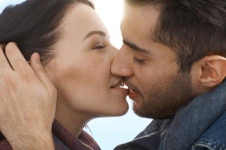 novios besandose: Foto del primer beso joven pareja de enamorados.