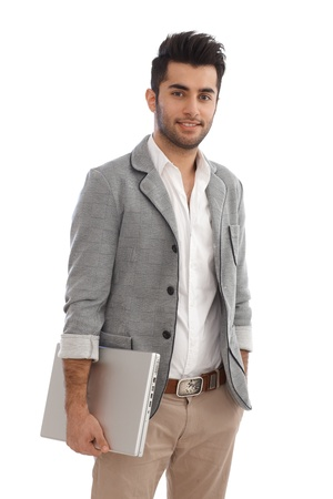 Young businessman holding laptop, standing with hands in pockets. Stock Photo - 17083846
