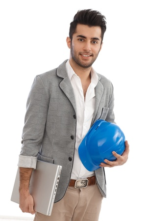 Handsome young engineer holding laptop and hardhat, smiling. Stock Photo - 17083854