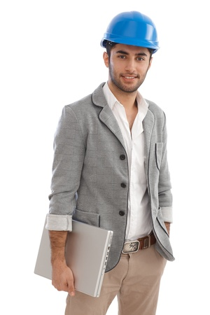 Handsome young architect holding laptop, smiling, wearing hardhat. photo