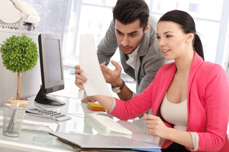 co worker: Young colleagues working together in office, looking at papers. Stock Photo