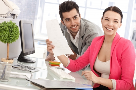 Happy young colleagues working together in office, laughing. Stock Photo - 17083801