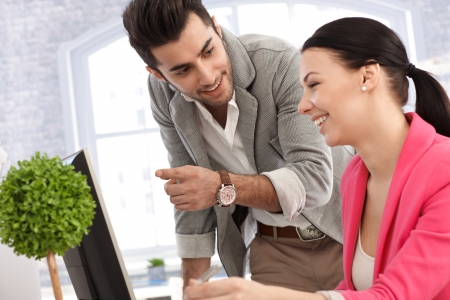 Young male and female colleague working together in the office, smiling happy. Stock Photo - 17083810