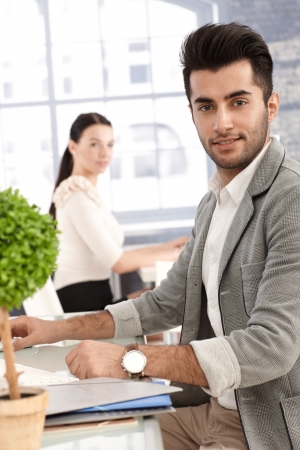 Portrait of handsome young office worker sitting at desk, smiling, female colleague watching in the background. Stock Photo - 17083807