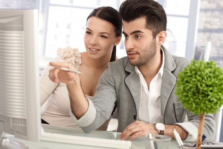Attractive young businesspeople working together at desk, using computer. Stock Photo - 17083809